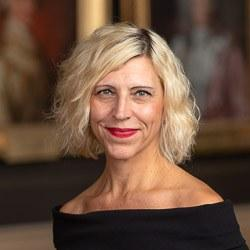 headshot of Ulrika Dahl - a white woman with wavy, silvery blonde hair in a bob, and a playful expression. She is wearing berry red lipstick and a black boat-neck top.